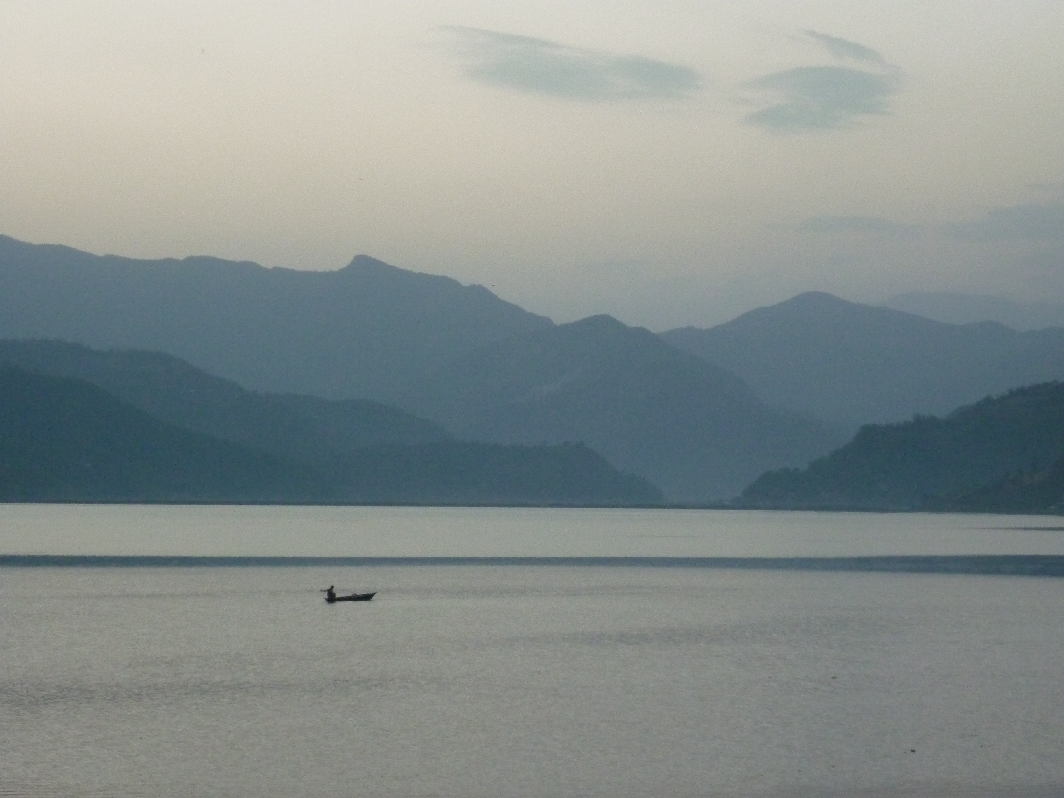 Pokhara // Auf dem Weg durch Nepal stoße ich auf Pokhara. Hippies waren die ersten, die diese Kleinstadt am See, im Schatten des Annapurna-Massivs, für sich entdeckten. Mittlerweile hat sich Pokhara zu einem beliebten Reiseziel entwickelt, trotzdem kann man dem Trubel mit Spaziergängen in die umliegende Natur entgehen. Beim Umwandern des Sees genieße ich die Einsamkeit, erkenne unglaubliche Graustufen, entdecke ich die Augen Gottes im Himmel (siehe Foto) und spüre so etwas wie Schöpfung in der Natur. Doch allzu viel Einsamkeit kann auch Trugbilder erschaffen und so reise ich weiter in die Hauptstadt von Nepal ...