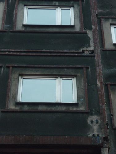 Außerirdischer - Mein erster Stopp war die Stadt Katowice. Kurz nachdem ich den Zug verlassen hatte, begann der Regen. Die grauschwarzen Fassaden der Häuser wurden dadurch noch trister und alles schrie nach Depressionen. Selbst der Außerirdische rechts unten im Bild zieht bei soviel Nässe im Hochsommer eine Fresse, als stünde er kurz vor dem Suizid. (Katowice)